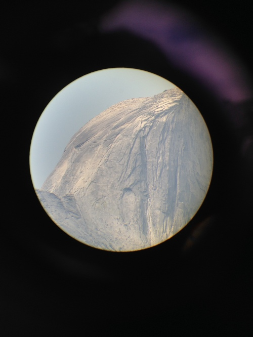 View through telescope of hikers ascending steel cables on Half Dome